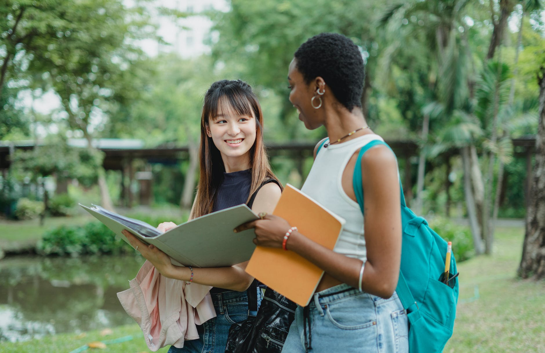 multiethnic female friends speaking while walking in park with notepads