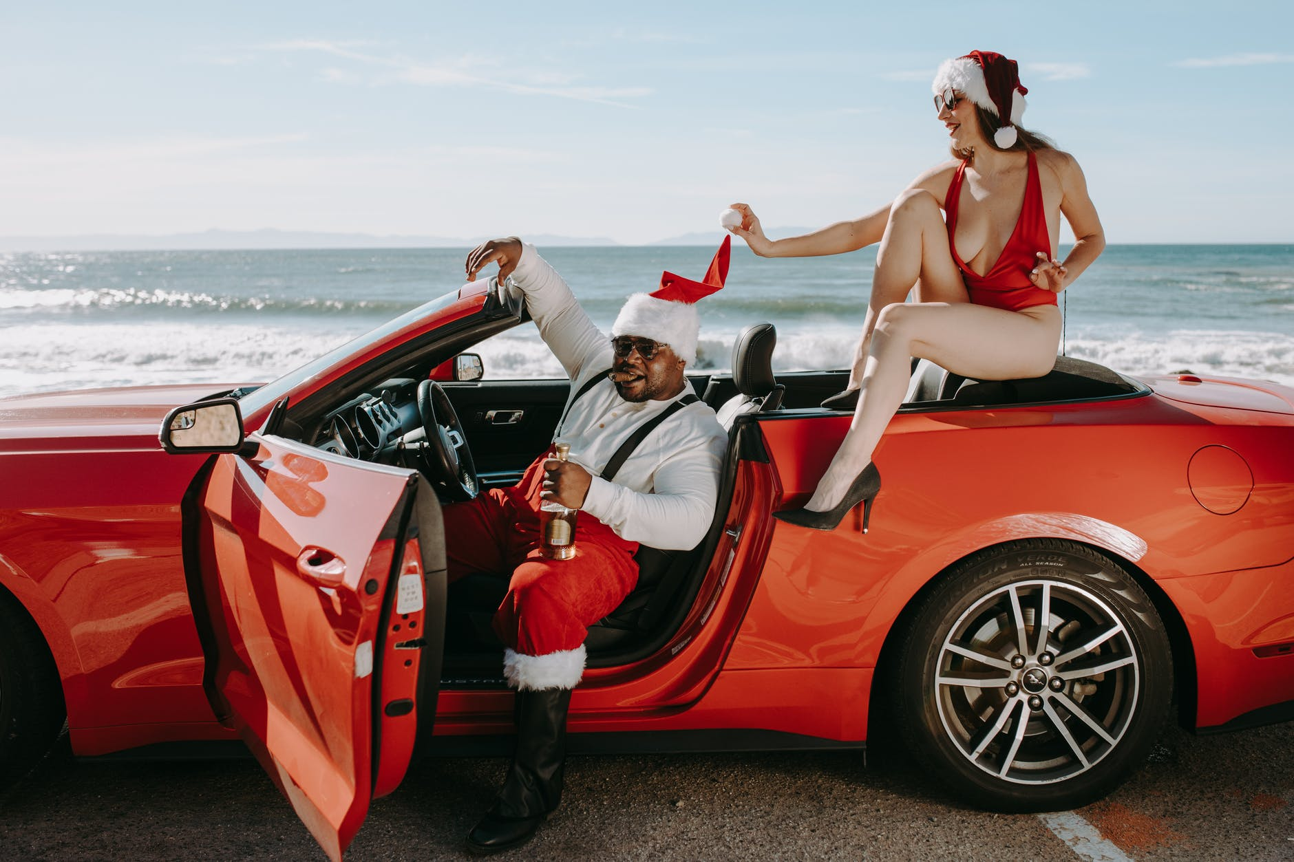 man and woman in santa outfits sitting in a red convertible car